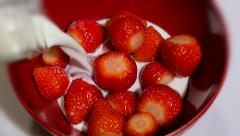 Pouring milk into a bowl of strawberries edge softness effect Stock Footage