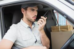 Delivery driver talking on walkie talkie in his van - stock photo