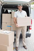 Delivery driver loading his van with boxes Stock Photos