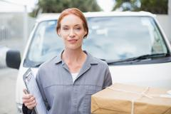 Stock Photo of Delivery driver smiling at camera by her van holding parcel