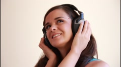 Cute beautiful girl in love listening romantic music on headphones smiling Stock Footage