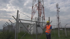 Engineer helmet and vest talking on mobile phone, electric panel issues, worker Stock Footage