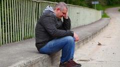 Depressed man sitting on the bridge Stock Footage