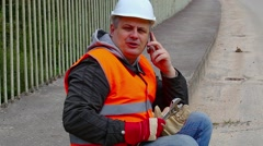 Worker with wrench and a telephone on the bridge Stock Footage