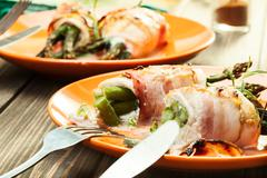 Baked fresh asparagus wrapped in chicken and bacon Stock Photos