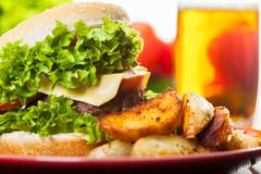 Cheeseburger with fried potatoes on a plate with beer glass Stock Photos