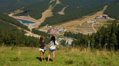Beautiful young girls on mountain looking at the mountains Stock Footage