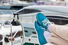 A pair of human legs in pants and bright blue topsiders on yacht Stock Photos
