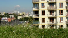 Green grass with city (buildings: high-rise block of flats) in the background -  Stock Footage