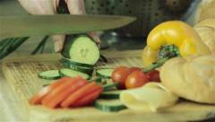 Female hands cutting cucumber into slice with fresh vegetables on background Stock Footage