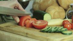 A woman is cutting a tomato into slices on wooden board Stock Footage