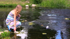 Girl run paper boat over fast flowing stream green park summer Stock Footage