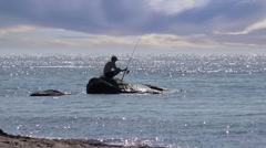 Fisherman fishing standing on rock by sea, HD Stock Footage