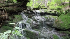 Water flowing in cascades on the mossy rock Stock Footage