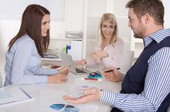 Business meeting: academics and controller sitting around a table. Stock Photos