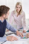 business meeting: young academics and controller sitting around a table. - stock photo