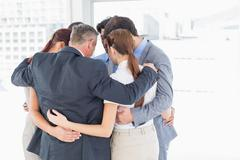 Business team all huddled together - stock photo