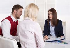 Financial business meeting: young married couple - adviser and clients. Stock Photos