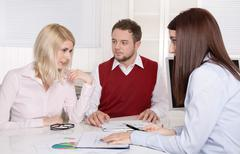 financial business meeting: young married couple - adviser and clients. - stock photo