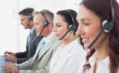 Stock Photo of Call center workers wearing headsets