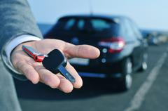 man offering a car key to the observer - stock photo