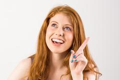 Stock Photo of Pretty redhead pointing and looking up