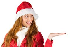 Festive redhead presenting with hand Stock Photos
