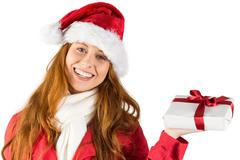 Stock Photo of Festive redhead holding a gift