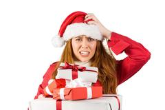 Festive stressed redhead holding gifts - stock photo