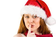 Festive redhead making quiet sign - stock photo