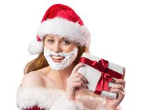 Festive redhead in foam beard holding gift - stock photo