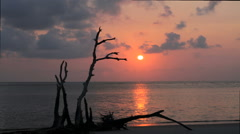 Sun and Clouds in motion during sunrise from a beach Stock Footage