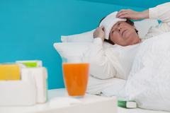 Senior woman laid ill in the bed with medicament and pillows, Stock Photos