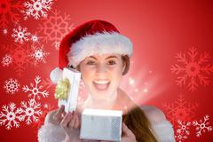 Composite image of sexy girl in santa costume opening a gift Stock Illustration
