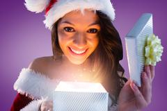 Composite image of sexy santa girl opening gift - stock illustration