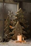 Atmospheric natural christmas decoration with wood and burning candles. Stock Photos