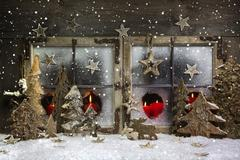 Mood and atmosphere: christmas window decoration in red with wood. Stock Photos