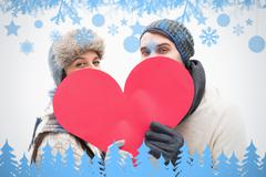 Composite image of attractive young couple in warm clothes holding red heart - stock illustration