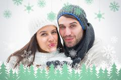 Composite image of attractive young couple in warm clothes blowing - stock illustration