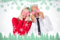 Stock Illustration of Composite image of silly couple holding hearts over their eyes