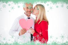 Stock Illustration of Composite image of handsome man holding paper heart getting a kiss from wife