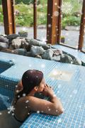 Composite image of brunette relaxing in a jacuzzi Piirros