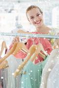 Composite image of happy female customer selecting clothes in store - stock illustration