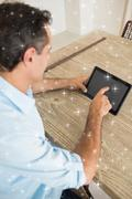 Composite image of concentrated man using digital table at home - stock illustration