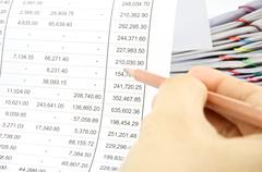 Man auditing account by pencil with pile of report Stock Photos