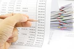 Man auditing account by pencil with pile of paperwork Stock Photos
