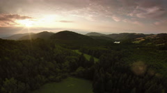Flying over hill and forest in sunset - stock footage