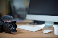 video editing workstation with video camera beside - stock photo