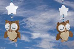 two sleeping felt owls on baby crib mobile - stock photo