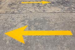 Yellow traffic arrow on concrete road Stock Photos